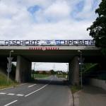 """Banner mit der Aufschrift """"Geschichte schreiben"""" hängt an einer Brücke."""